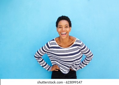 Portrait of attractive young african american young woman smiling against blue wall