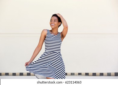 Portrait of attractive young african american woman laughing in striped dress