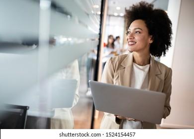 Portrait d'une jeune femme d'affaires africaine séduisante souriante, debout près des fenêtres de son bureau