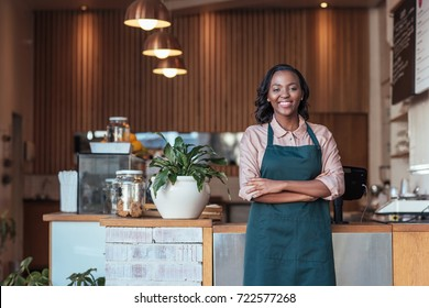 Portrait of an attractive young African female entrepreneur smiling and standing welcomingly in her trendy cafe