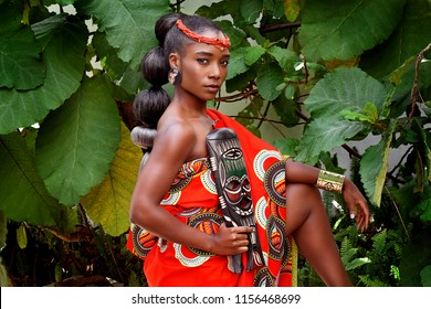 Portrait of an attractive young African woman wearing traditional clothes and holding a mask while sitting outside with foliage in the background