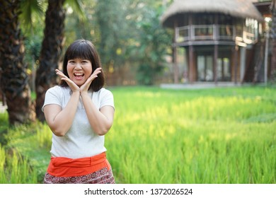 Portrait of attractive young Asian bangs girl standing in front of the rice field background and look like feel happiness and smiling.