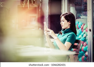 Portrait of attractive young Asian business woman sitting in cafe and using mobile smart phone in her hands, process color.