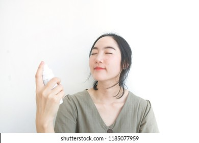 Portrait of attractive young asian lady smiling and using mist spray white background.