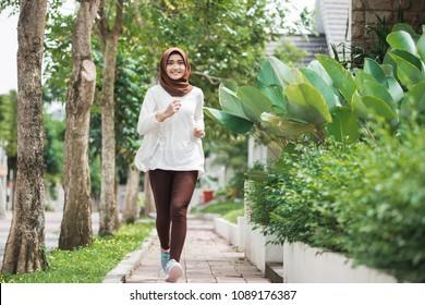 portrait of attractive young asian muslim woman running and exercising outdoor