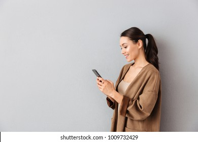Portrait of an attractive young asian woman using mobile phone while standing with copy space over gray background