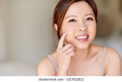 Portrait of an attractive young Asian woman applying cream to her cheek while getting ready in the morning