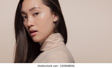 Portrait of attractive young asian woman with brown hair against beige background. Korean female model looking at camera.