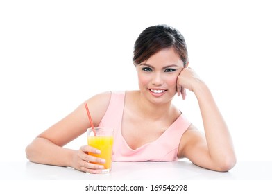 Portrait of an attractive young Asian woman holding a glass of orange juice over white background.