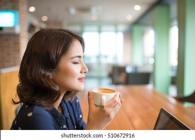 Portrait of attractive young asian woman drinking coffee