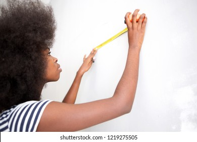 Portrait of attractive young black woman doing home improvement
