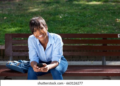 Portrait of attractive young black woman sitting on bench outside with mobile phone