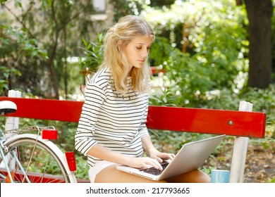 Portrait of attractive young blogger working on laptop while sitting at park.