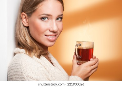 Portrait of an attractive young blond woman holding a hot cup of tea.