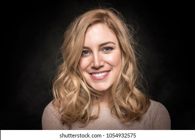 Portrait of an attractive young blonde woman on a dark background.