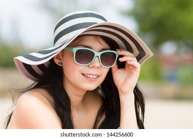 Portrait of attractive young brunette girl in fashionable turquoise sunglasses and hat