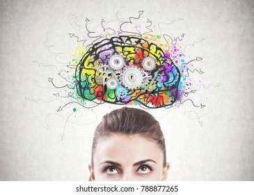Portrait of an attractive young brunette woman wearing a brown blouse and looking upwards at a colorful brain sketch with cogs on it.