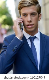 Portrait of an attractive young businessman on the phone in urban background, wearing blue suit and tie. Blonde hair