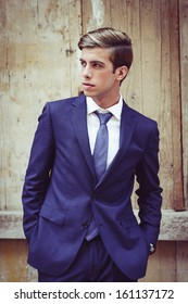 Portrait of an attractive young businessman in urban background wearing blue suit a necktie. Blonde hair