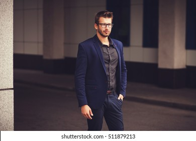 Portrait of an attractive young businessman in urban background wearing blue suit.