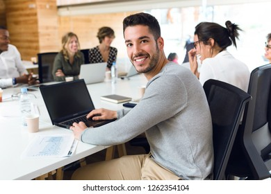 Portrait of attractive young businessman working with laptop while looking at camera on coworking place.
