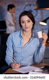 Portrait of attractive young businesswoman sitting at desk, writing, drinking coffee.