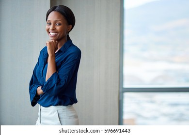 Portrait of an attractive young businesswoman smiling while standing with her hand on her chin by windows in a modern office