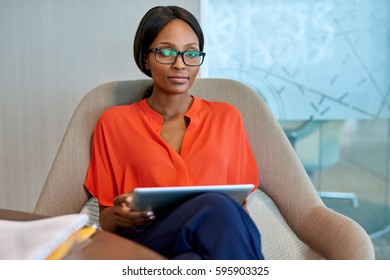 Portrait of an attractive young businesswoman wearing glasses using a digital tablet while sitting in a chair in a modern office