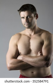 Portrait of an attractive young caucasian athlete. The man is posing and flexing his muscles. The guy is shirtless and is wearing red workout shorts.