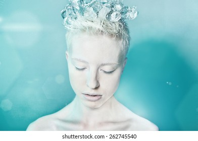 portrait of attractive young caucasian blond woman wearing wreath from ice cubes on her head studio shot isolated on blue.