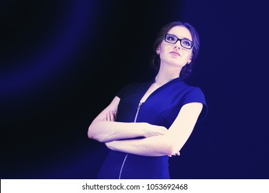 Portrait of attractive young caucasian business woman with crossed arms on black blue background