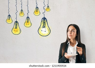 Portrait of attractive young caucasian businesswoman on concrete background with drawn lamps. Idea and achievement concept