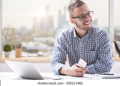 Portrait of attractive young caucasian man using smartphone while sitting at office table with laptop computer and other items