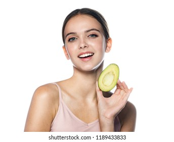 portrait of attractive young caucasian smiling cheerful woman isolated on white studio shot eating avocado lookıng at camera toothy smıle