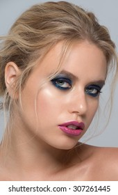 Portrait of attractive young caucasian woman with stylish blue makeup
