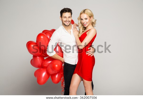 Portrait of attractive young couple posing on grey background and holding balloons heart. Valentine's day.