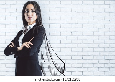 Portrait of attractive young european businesswoman with drawn cape on brick wall background. Leadership and leader concept