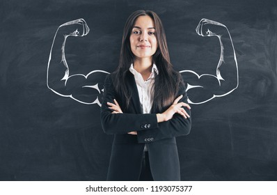 Portrait of attractive young european businesswoman with drawn muscly arms. Confidence and power concept