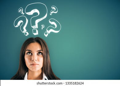 Portrait of attractive young european businesswoman with question mark drawings on green background. Confusion and challenge concept