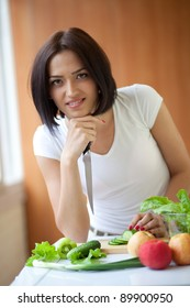 Portrait of an attractive young female cooking in the kitchen at home
