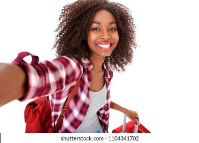 Portrait of attractive young female traveler taking selfie on white background