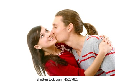Portrait of attractive young girl embracing her boyfriend while he kissing her cheek