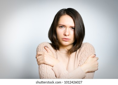 Portrait of an attractive young girl freezing. All on gray background.