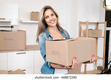 Portrait of attractive young girl holding box in new home and looking at camera