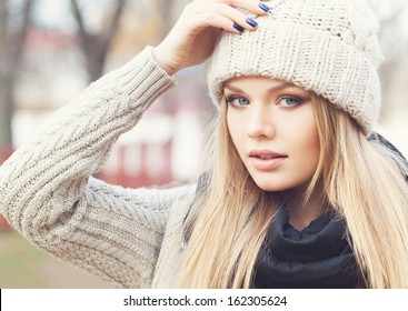 Portrait of attractive young girl in knitted clothes with hand next to her cap. Looking at camera. Outdoors