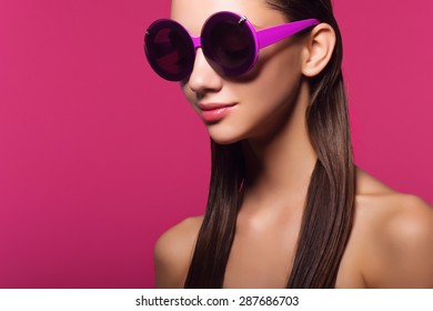 Portrait of an attractive young girl in round glasses on a pink background in studio