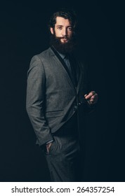 Portrait of an Attractive Young Guy with Beard and Mustache, Wearing Classy Formal Suit, Holding his Eye Wear with the Other Hand in his Pocket. Isolated on Black.
