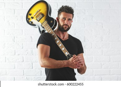 Portrait of attractive young guy with electric guitar on shoulder. White brick wall background