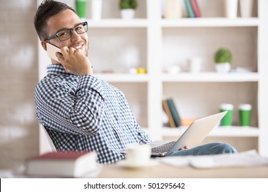 Portrait of attractive young guy in glasses sitting at office desk with laptop computer and talking on cellular phone. Communication concept
