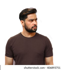 Portrait of an attractive young Indian man with beard looking away.
